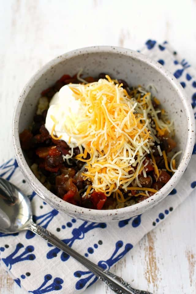 beans and rice in a bowl with sour cream and cheese