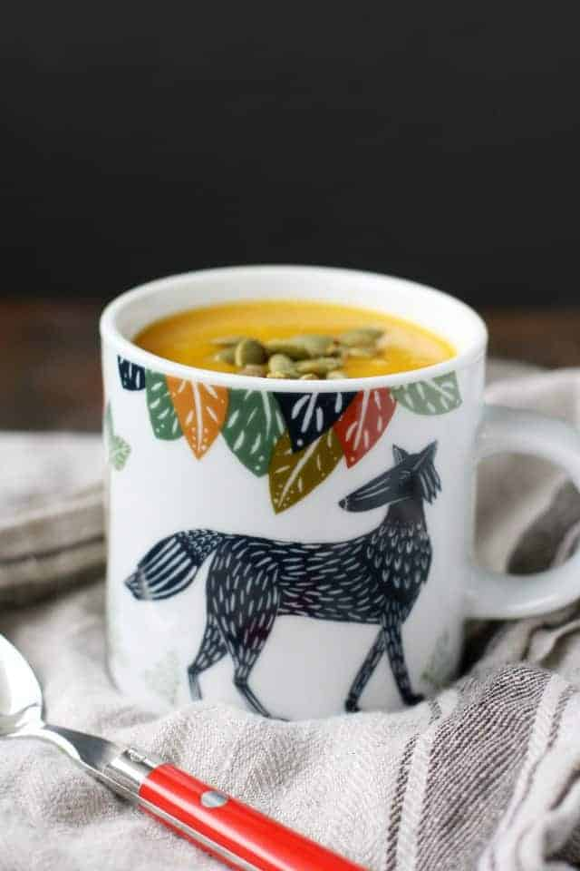 mug of vegan butternut squash soup with pepitas on top