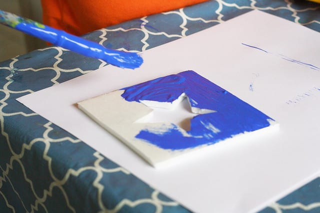 painting blue paint on a foam stamp