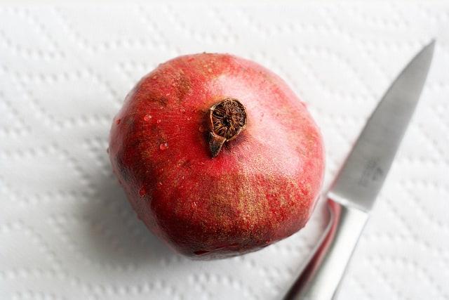 whole pomegranate next to a knife