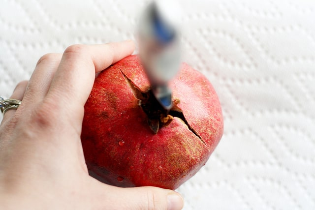 pomegranate being opened by a sharp kitchen knife