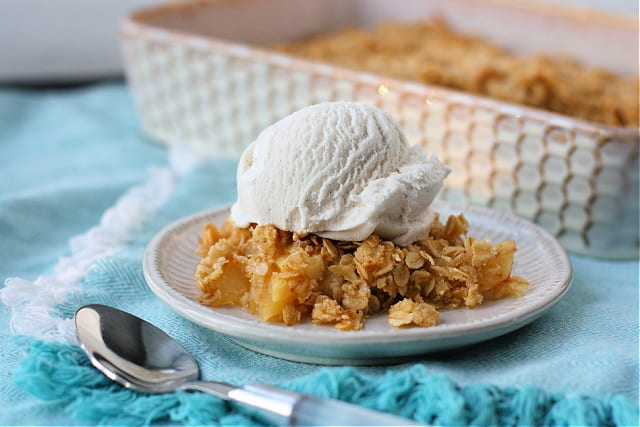 vegan apple crisp on a white plate with ice cream