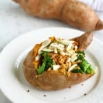 A healthy baked sweet potato topped with broccoli, almonds, and red pepper flakes.