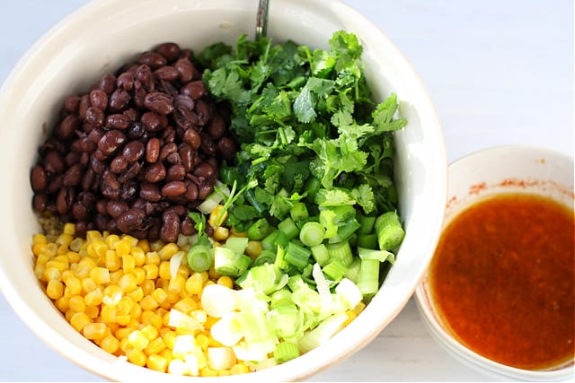 quinoa salad ingredients in bowl with dressing