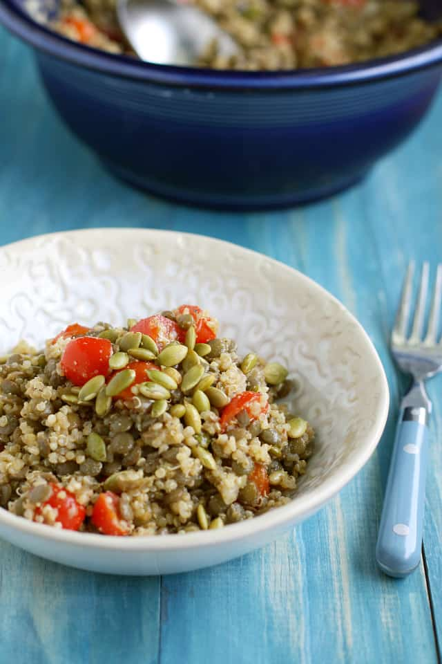 A fresh salad made with quinoa, lentils, tomatoes, and pepitas