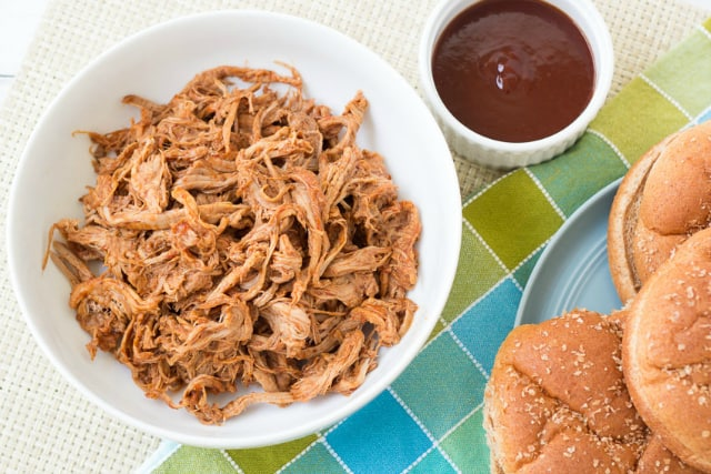 Slow cooker pulled pork with barbecue sauce in a white serving dish