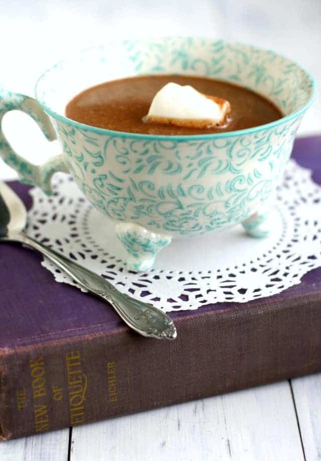 tea cup of hot chocolate sitting on a purple book