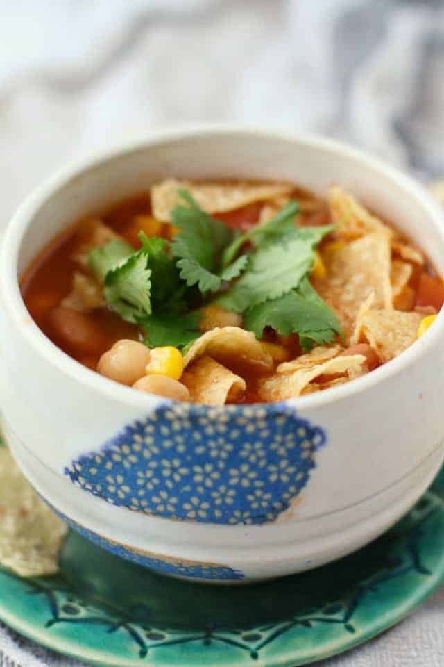 vegan tortilla soup in a white bowl with cilantro on top