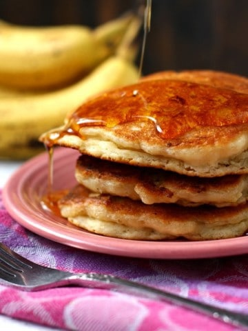 fluffy vegan banana pancakes with maple syrup on a pink plate