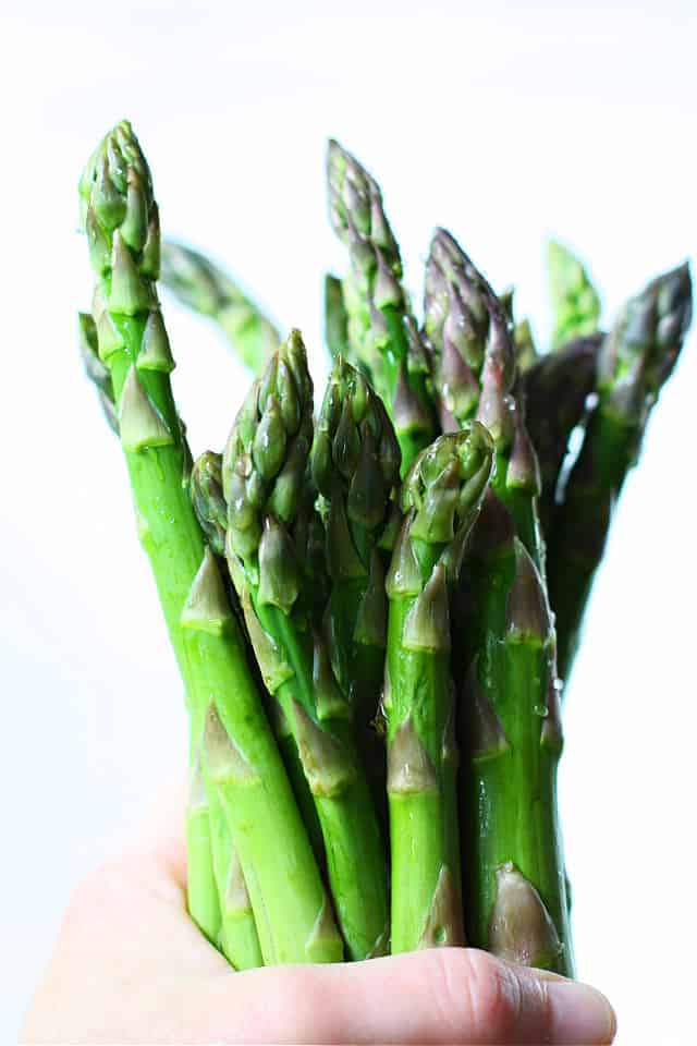 bunch of asparagus held in one hand