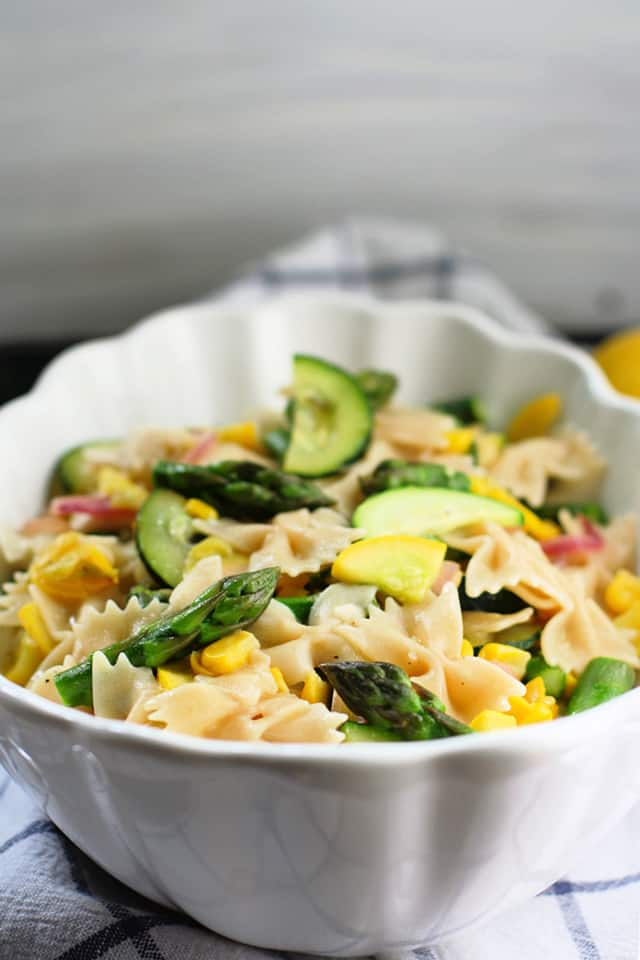 spring vegetable pasta in a white bowl