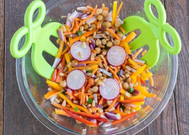 chickpea salad in a glass bowl with green tongs