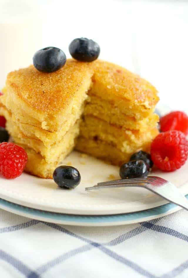 Our new favorite pancake recipe - cornmeal pancakes topped with fresh berries! Easy to make, and perfect for the weekend! #pancakes
