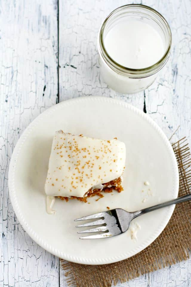 a piece of frosted zucchini cake on a white plate