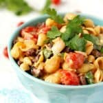Southwest pasta salad with tri-color beans, tomatoes, cilantro, peppers, and a creamy, spicy, dressing. Delicious and easy!