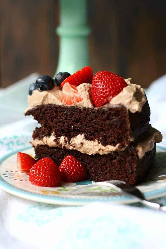slice of gluten free chocolate zucchini cake with berries on a plate