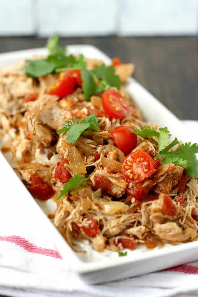 slow cooker taco chicken with tomatoes on a white tray