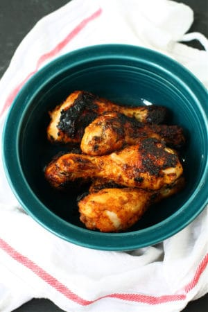 grilled chicken legs in a teal bowl