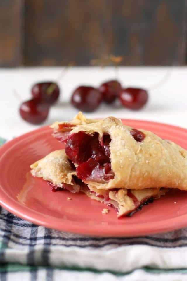 cherry hand pies on a pink plate
