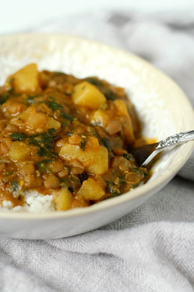potato lentil curry in a white bowl with a fork