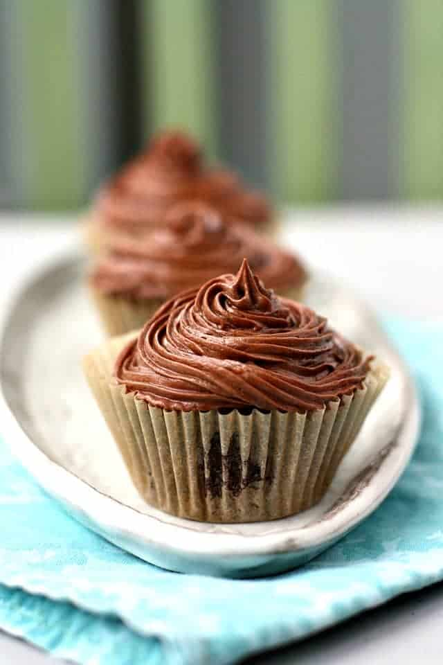 vegan chocolate frosting on a cupcake on a white tray