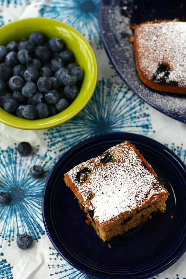 slice of blueberry cake and bowl of blueberries