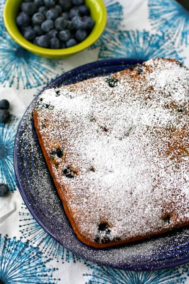 blueberry cake on a dark blue platter