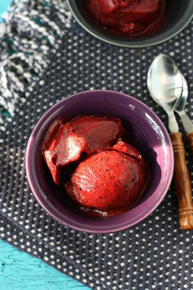 cherry berry sorbet in a violet bowl with a spoon