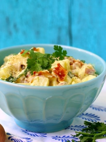 potato salad with bacon in a light blue bowl