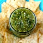 salsa verde on a blue plate with tortilla chips