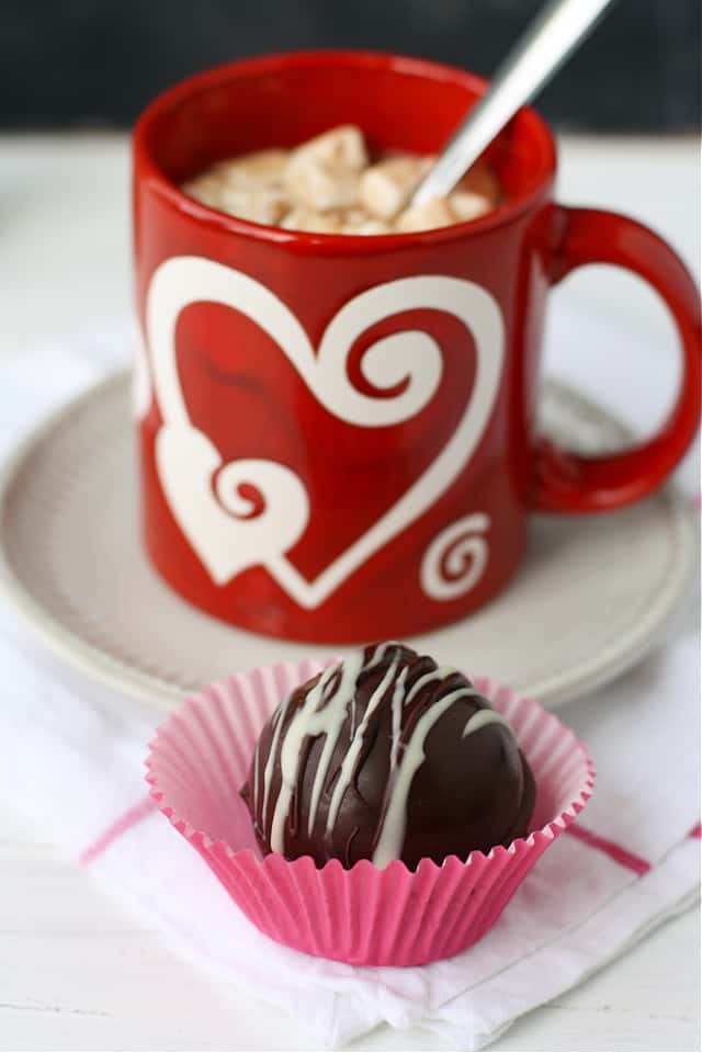 mug of vegan hot cocoa with chocolate bomb in front of mug