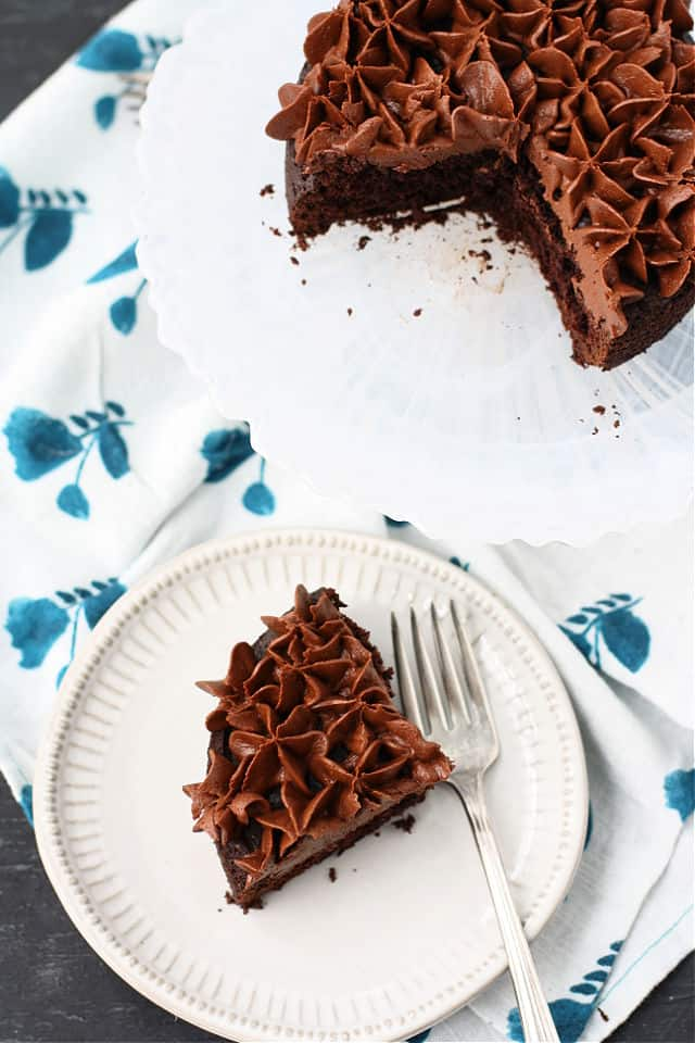 slice of chocolate cake with frosting on a plate on a flowered napkin