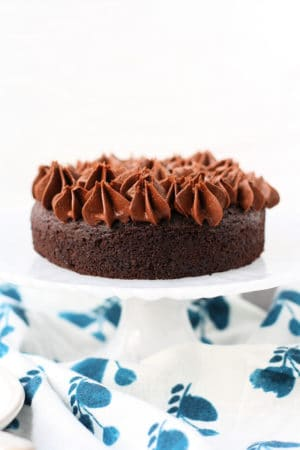 small chocolate cake on a white cake stand