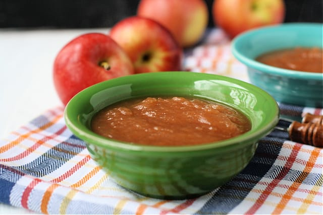 bowls of cinnamon applesauce with apples in the background