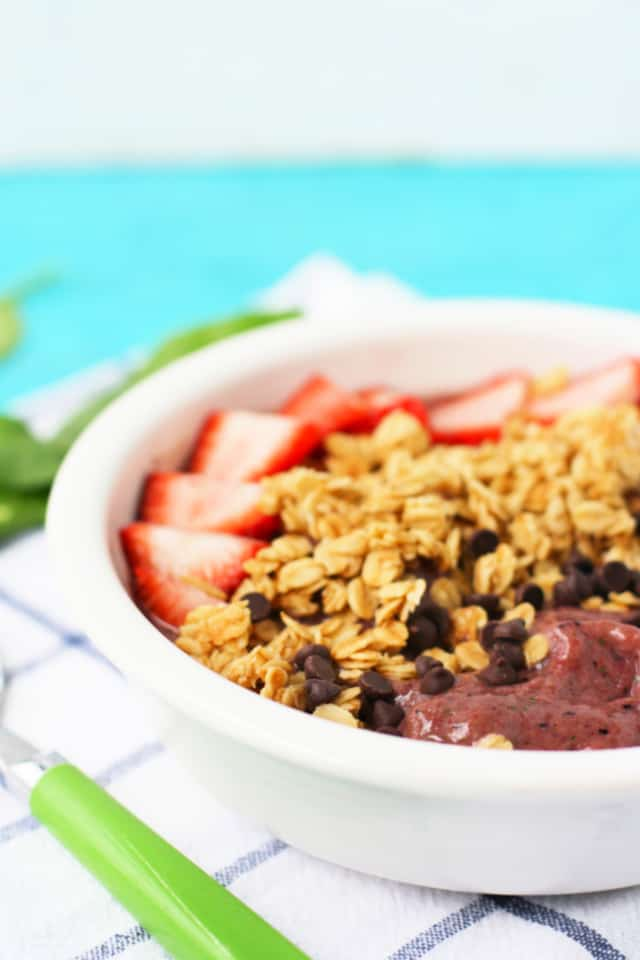 dairy free berry smoothie bowl with spinach in a white bowl