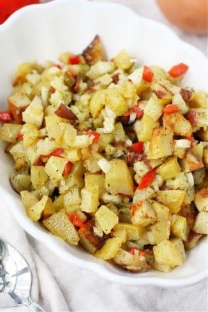dill pickle potato salad in a white bowl