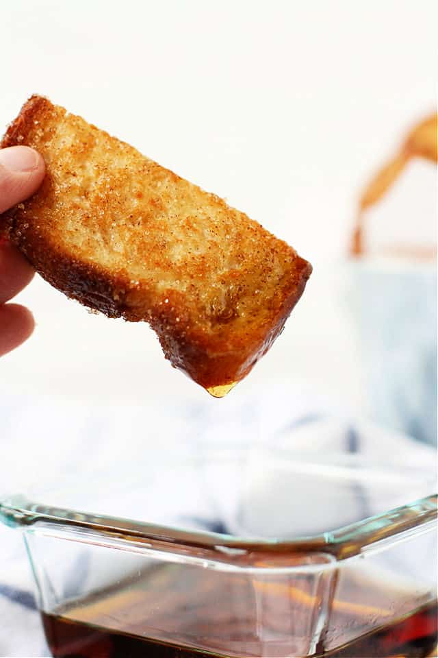 french toast stick being dipped into syrup