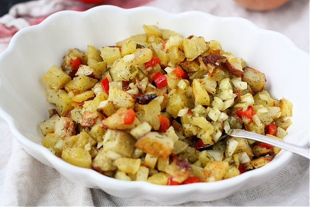 roasted potato salad with dill pickles in a white serving dish