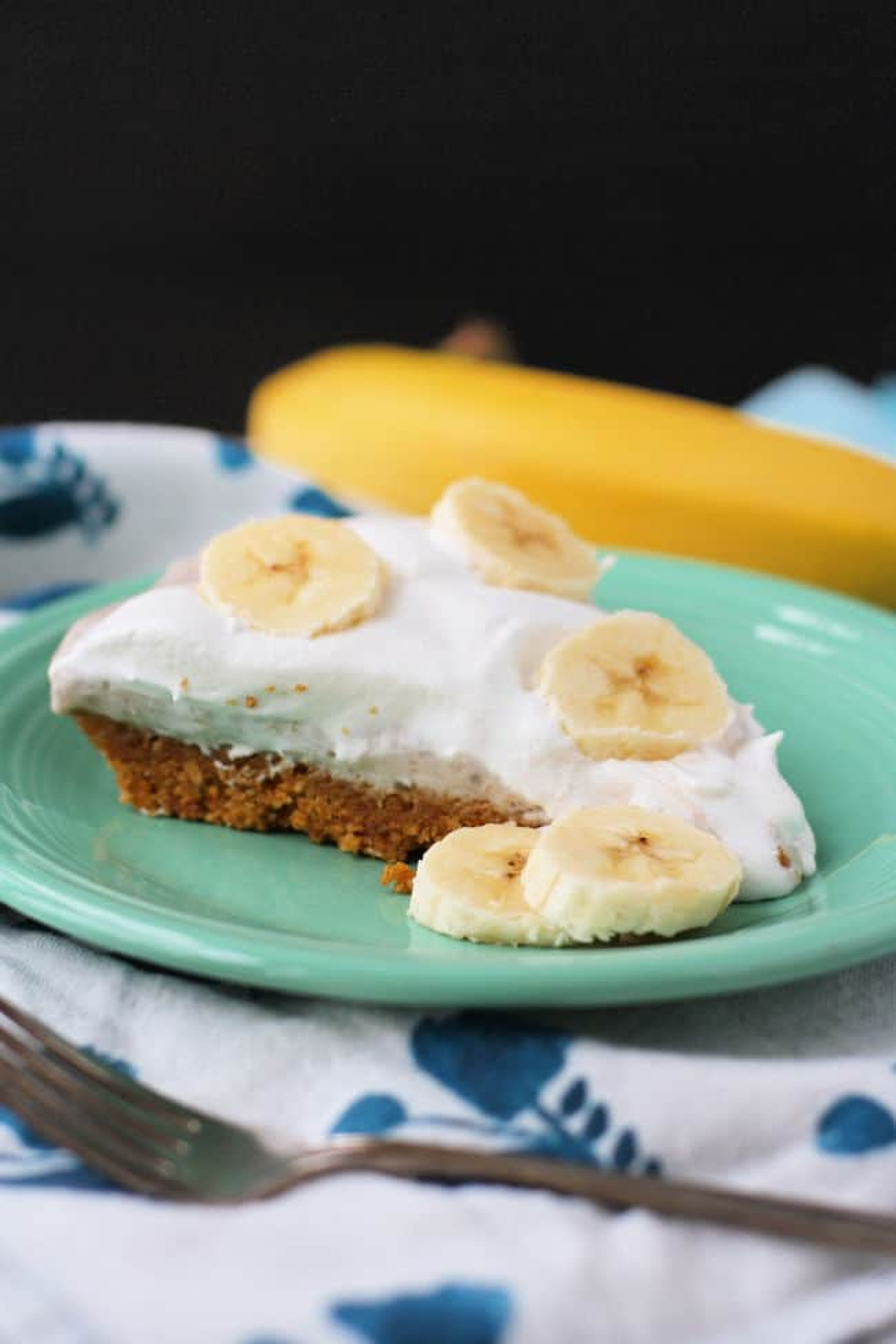 Rebanada de pastel de crema de plátano en una placa verde