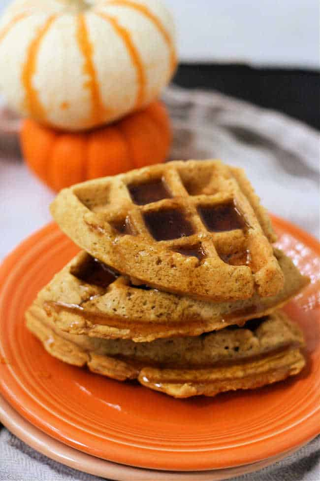 waffles with syrup on them on an orange plate