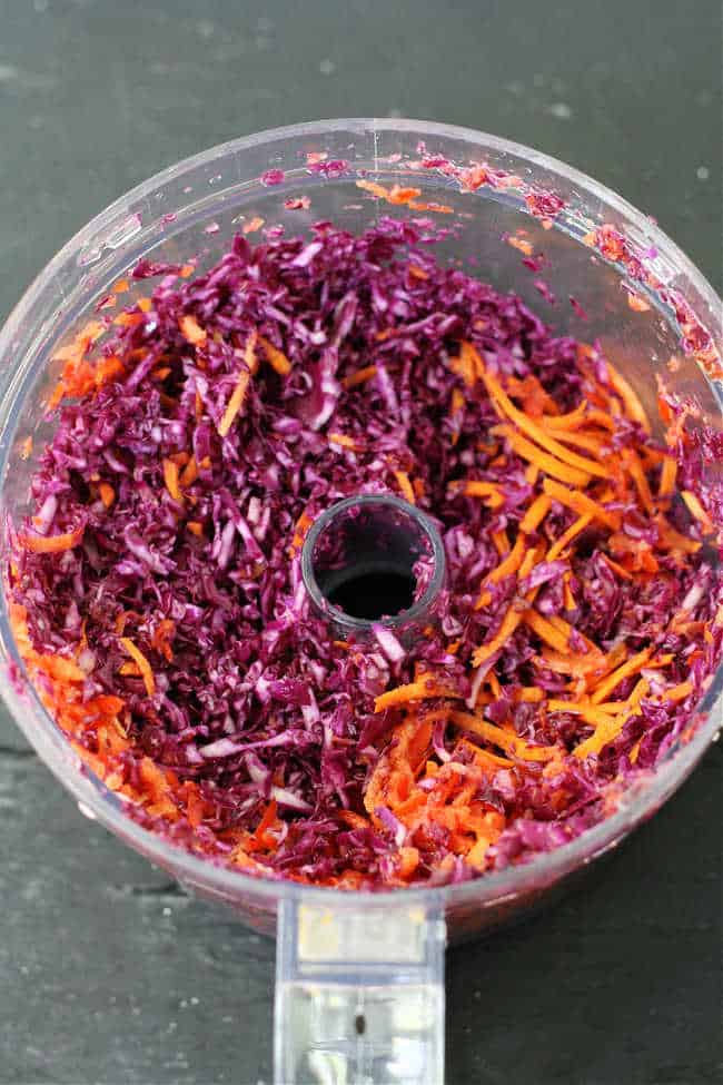 red cabbage and carrots in a food processor