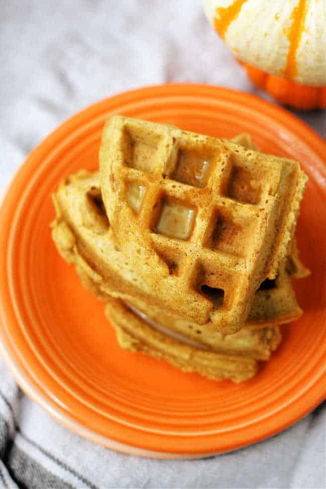 vegan pumpkin waffles on an orange plate