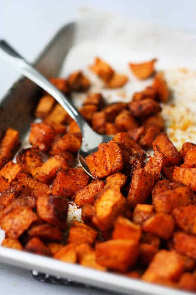 roasted sweet potatoes on a baking sheet with a spoon